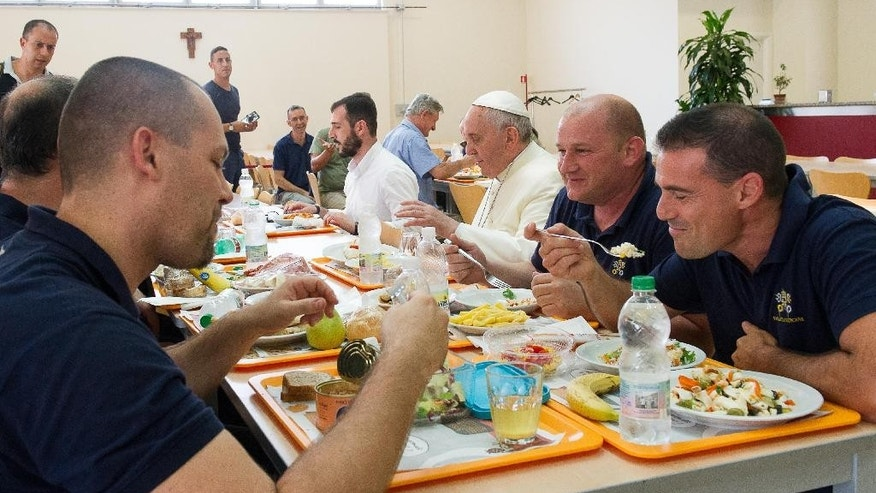 "In this photo provided by the Vatican newspaper L'Osservatore Romano, Pope Francis, third from right, has lunch at the Vatican workers' cafeteria, Friday, July 25, 2014. Pope Francis got a free meal on Friday when he popped in unannounced at the Vatican workers' cafeteria and lined up, tray in hand, along with stunned diners. Cashier Claudia Di Giacomo told Vatican newspaper L'Osservatore Romano that when Francis presented his tray with a plate of cod fish, a bowl of fusilli pasta without sauce, a side of grilled tomatoes and ""just a few"" french fries she ""didn't have the courage to hand him the bill."" Francis chatted with his tablemates five Vatican pharmacy stock clerks. His tip? A papal blessing and photos snapped with diners, said the cafeteria chef, Franco Paini. The pope usually dines at the Vatican guest house where he lives. (AP Photo/L'Osservatore Romano)"