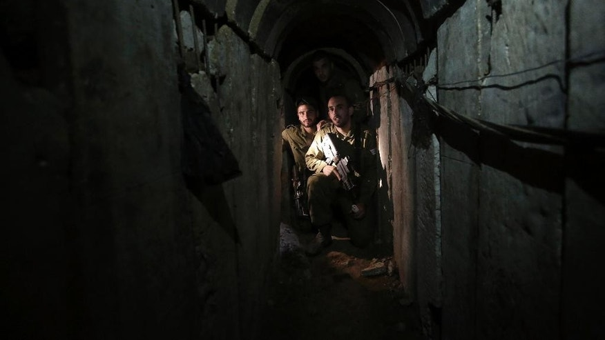 "FILE - In this Sunday, Oct. 13, 2013 file photo, Israeli soldiers walk through a tunnel discovered near the Israel Gaza border. They've been dubbed ""lower Gaza,"" compared to the Underground, the Metro or the subway and depicted as a bone-chilling, strategic threat to Israel. Hamas' web of tunnels is taking center stage in the relentless conflict between the militant group and Israel, with Israel's ground offensive placing their destruction as a key objective. (AP Photo/Tsafrir Abayov, File)"