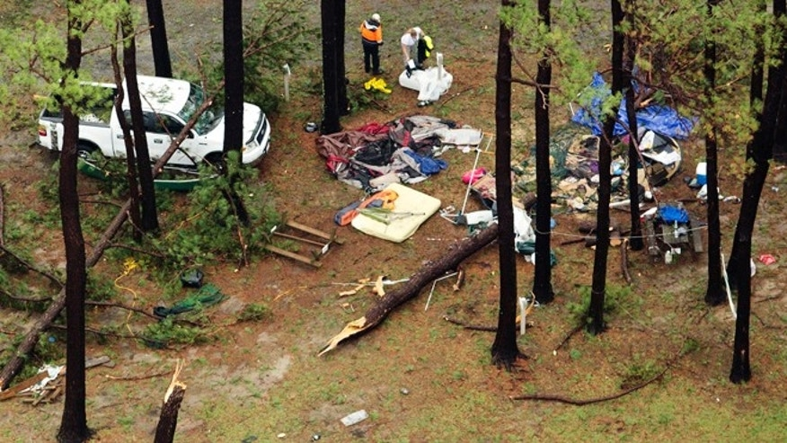 In this aerial photo people inspect damage at Cherrystone Family Camping & RV Resort in Northampton County, Thursday, July 24, 2014, near Cheriton, Va., after a severe storm swept through the area. Softball-sized hail and rain toppled dozens of trees and flipped recreational vehicles at the campground Thursday, killing two people and injuring more than two dozen, officials said. (AP Photo/The Virginian-Pilot, L. Todd Spencer)  MAGS OUT