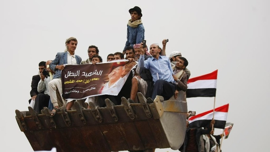 Yemenis ride in the bucket of a bulldozer during the funeral procession of army commander Brigadier General Hameed Al-Qushaibi, who was killed in a recent fighting against Shiite fighters, in Sanaa, Yemen, Wednesday, July 23, 2014. (AP Photo/Hani Mohammed)