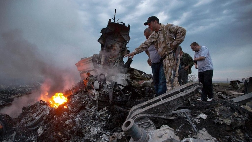 FILE - In this Thursday, July 17, 2014 file photo, people inspect the crash site of a passenger plane near the village of Grabovo, Ukraine. All 298 people aboard the Malaysia Airlines Flight 17 traveling from Amsterdam to Kuala Lumpur were killed. (AP Photo/Dmitry Lovetsky)