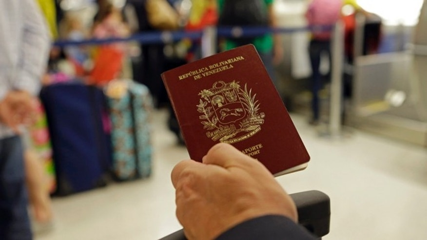 In this photo taken Wednesday, June 25, 2014, a passenger holds his Venezuelan passport as he prepares to travel to Venezuela at Miami International Airport in Miami. American Airlines announced that it will cut nearly 80 percent of its flights to Venezuela in a dispute over revenue being held by the South American country. American said that beginning July 2 it will operate 10 flights per week instead of the current 48. And it will only fly to Venezuela from Miami, scrapping flights from New York, Dallas and San Juan, Puerto Rico. (AP Photo/Alan Diaz)