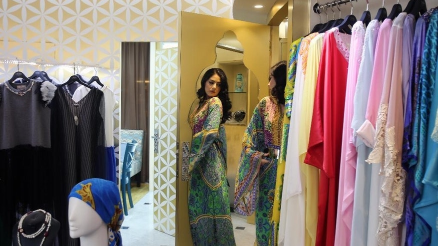 In this Tuesday, July 14, 2014 photo, fashion designer Tamara Al Gabbani looks at one of her designs in the Jalabiya collection at the Be You boutique in Dubai, United Arab Emirates. Ramadan, Islam's holiest month, is a boon for retailers in the Middle East, South Asia and beyond. And while some Muslims welcome it as a positive sign, others see it as commercialization of a sacred time of year, threatening to subvert its very nature. (AP Photo/Kamran Jebreili)