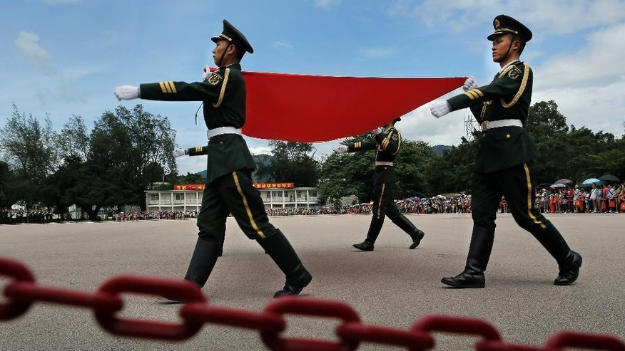 In this June 29, 2014 photo, soldiers carry a Chinese national flag at a military base during an open day event of the Chinese People's Liberation Army (PLA) in Hong Kong. Many in this prosperous city had already feared that Hong Kong's future as an open society as well as a semiautonomous part of China was in jeopardy in the face of perceived growing intervention from Beijing. (AP Photo/Vincent Yu)
