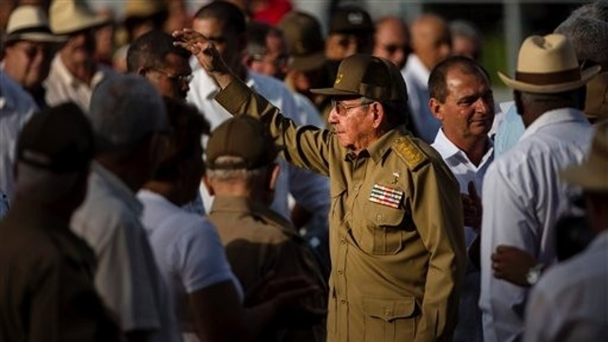 Cuba's President Raul Castro, center, waves at the end of an event celebrating Revolution Day in Artemisa, Cuba, Saturday, July 26, 2014. Cuba marks the 61st anniversary of the July 26, 1953 rebel attack led by Fidel and Raul Castro on the Moncada military barracks. The attack is considered the beginning of the revolution that culminated with dictator Fulgencio Batista's ouster. (AP Photo/Ramon Espinosa)