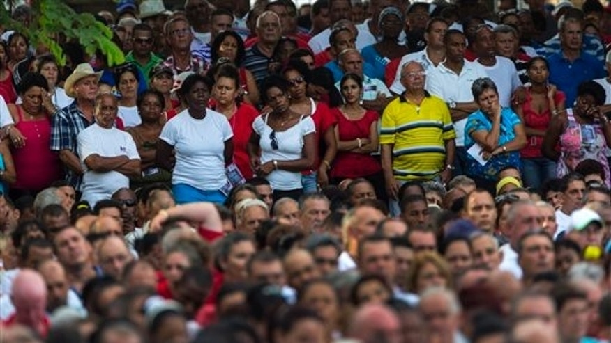 People attend an event celebrating Revolution Day in Artemisa, Cuba, Saturday, July 26, 2014. Cuba marks the 61st anniversary of the July 26, 1953 rebel attack led by Fidel and Raul Castro on the Moncada military barracks. The attack is considered the beginning of the revolution that culminated with dictator Fulgencio Batista's ouster. (AP Photo/Ramon Espinosa)