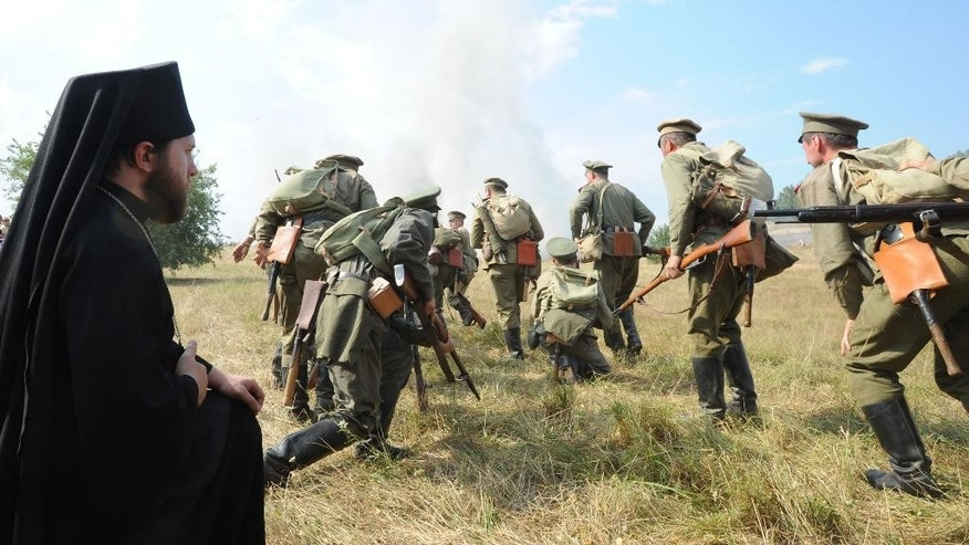 Actors dressed as Russian soldiers perform an attack, as another actor dressed as an orthodox priest , left, prays, during the re-enactment of the 1914 Battle of Tannenberg in Szkotowo, Poland, Sunday, July 27, 2014, marking the 100th anniversary of the beginning of World War I. History enthusiasts from across Europe gathered re-enact  the Battle of Tannenberg, an engagement between the Russian and German Empires in the first days of World War I.  (AP Photo/Alik Keplicz)