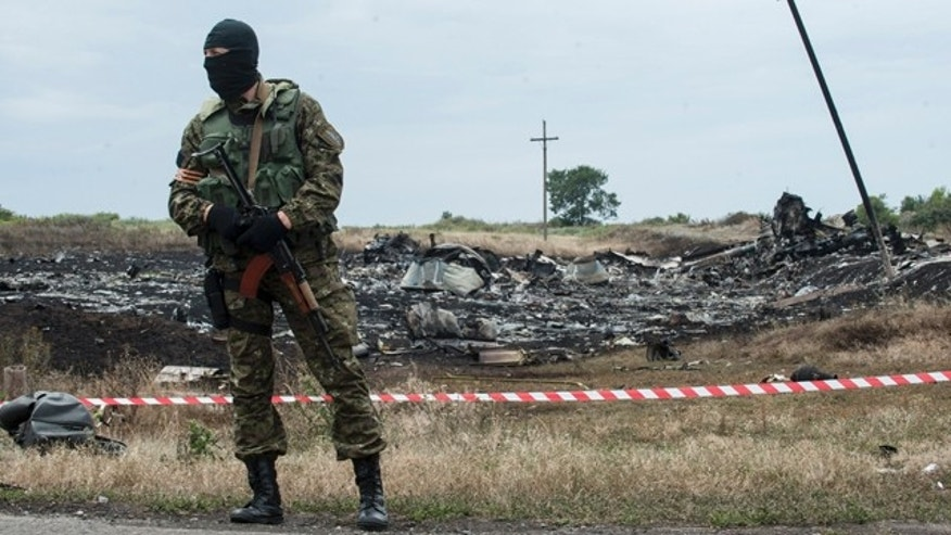 FILE - This July 19, 2014, file photo shows pro-Russian fighter guarding the crash site of Malaysia Airlines Flight 17 near the village of Hrabove, eastern Ukraine. (AP Photo/Evgeniy Maloletka, File)