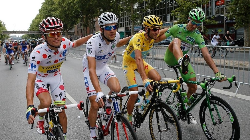 Vincenzo Nibali of Italy, wearing the overall leader's yellow jersey, second right,  Peter Sagan of Slovakia, wearing the best sprinter's green jersey, right. Rafal Majka of Poland, wearing the best climber's dotted jersey, left and Thibaut Pinot of France, wearing the best young rider's white jersey, cycle at the front of the field at the start of the twenty-first and last stage of the Tour de France cycling race over 137.5 kilometers (85.4 miles) with start in Evry and finish in Paris, France, Sunday, July 27, 2014.   (AP Photo/Christophe Ena)