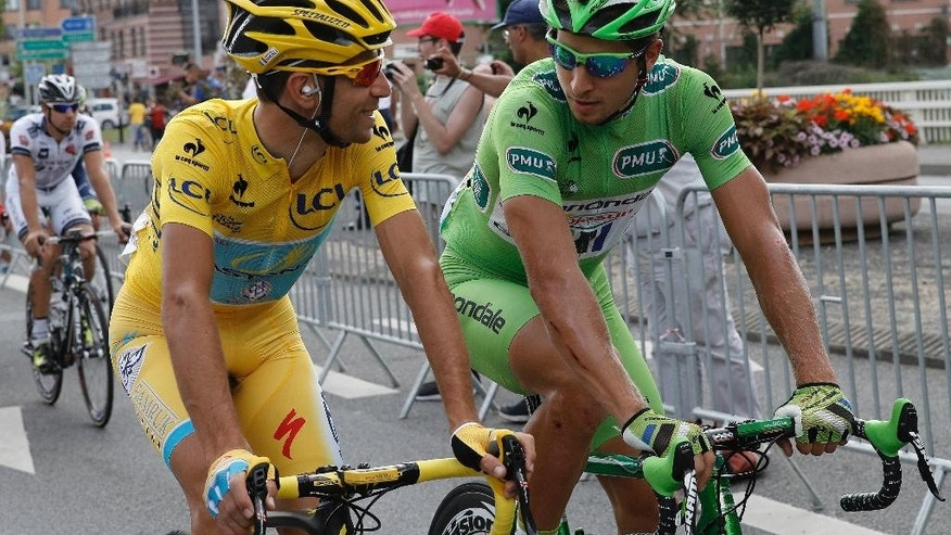 Vincenzo Nibali of Italy, wearing the overall leader's yellow jersey, left,  chats with Peter Sagan of Slovakia, wearing the best sprinter's green jersey, right. as they cycle at the front of the field at the start of the twenty-first and last stage of the Tour de France cycling race over 137.5 kilometers (85.4 miles) with start in Evry and finish in Paris, France, Sunday, July 27, 2014.  (AP Photo/Christophe Ena)