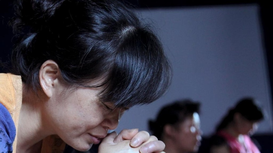 In this photo taken July 16, 2014, church members pray in a private room in Jiu'en Tang, a Christian church, in the Shuitou township in Wenzhou in eastern China's Zhejiang province. Across Zhejiang province, which hugs China's rocky southeastern coast, authorities have toppled, or threatened to topple, crosses at more than 130 churches. (AP Photo/Didi Tang)