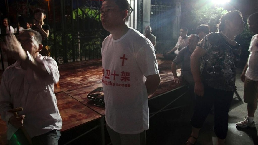 "In this photo taken July 16, 2014, a church member wears a T-shirt with the Chinese words ""Defend the cross"" as he stakes out overnight to protect the cross from being demolished at a Christian church in Ao'jiang, Pingyang county of Wenzhou in eastern China's Zhejiang province. Across Zhejiang province, which hugs China's rocky southeastern coast, authorities have toppled, or threatened to topple, crosses at more than 130 churches. (AP Photo/Didi Tang)"
