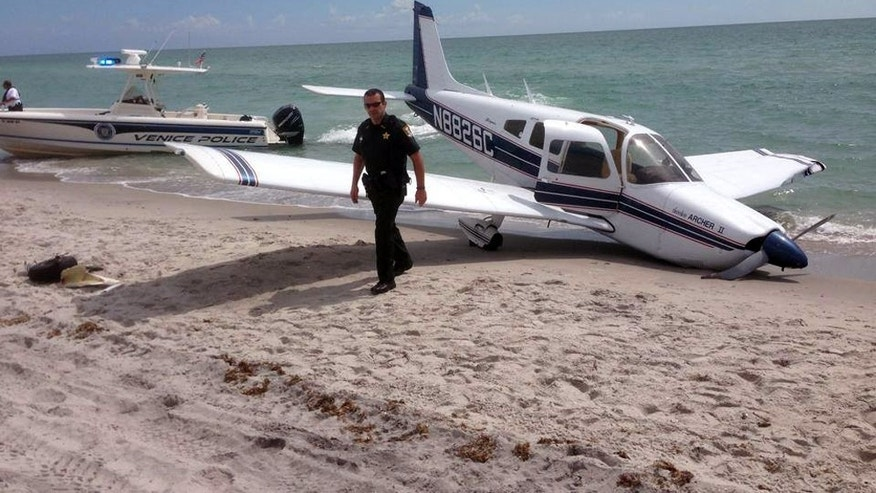 This Sunday, July 27, 2014, photo provided by the Sarasota County Sheriff's Office shows emergency personnel at the scene of a small plane crash in Caspersen Beach in Venice, Fla. Authorities say a father was killed and his daughter seriously injured while walking on the sand when a small plane crash landed along Florida's Gulf Coast near Venice Beach. (AP Photo/Sarasota County Sheriff's Office)
