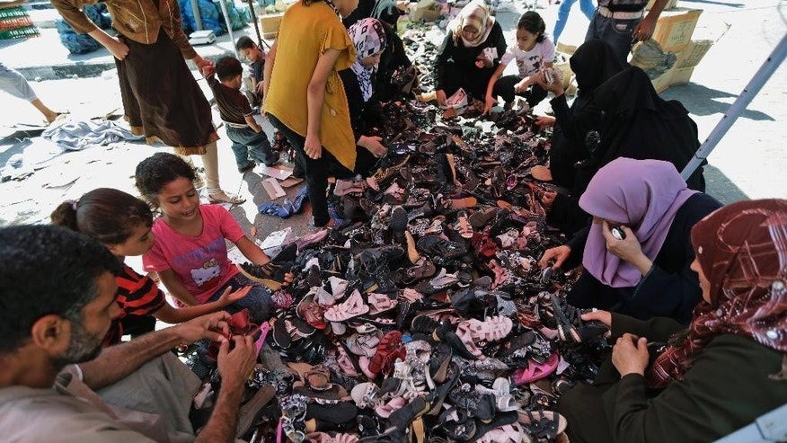 Palestinian women and children search shoes at a stall in Jebaliya refugee camp's market, northern Gaza Strip, Sunday, July 27, 2014. During normal times, families in Gaza would be busy now with preparations for Eid al-Fitr, the three-day holiday marking the end of the Muslim fasting month of Ramadan. Traditionally, children get new clothes, shoes and haircuts, and families visit each other. In the outdoor market, vendors set up stands with clothes and shoes, but said business was slow. (AP Photo/Lefteris Pitarakis)
