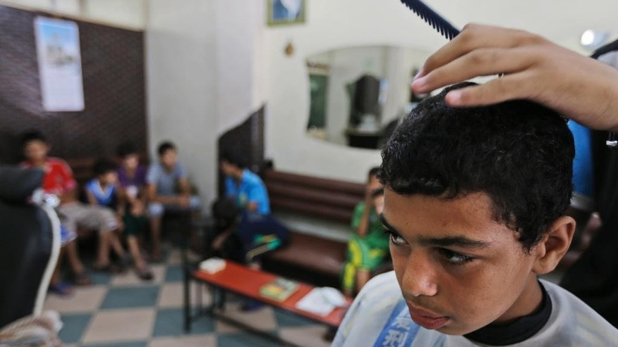 Palestinian Muhammed Hasouna, 14, has his hair cut at a barber shop in preparation for Eid, in Jebaliya refugee camp, northern Gaza Strip, Sunday, July 27, 2014. During normal times, families in Gaza would be busy now with preparations for Eid al-Fitr, the three-day holiday marking the end of the Muslim fasting month of Ramadan. Traditionally, children get new clothes, shoes and haircuts, and families visit each other. In the outdoor market, vendors set up stands with clothes and shoes, but said business was slow. (AP Photo/Lefteris Pitarakis)