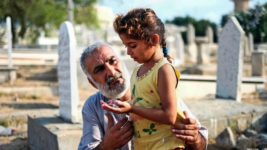 A relative guides a girl in prayer at the grave of their loved one in a cemetery in Gaza city, northern Gaza Strip, Monday, July 28, 2014. Monday marked the beginning of the three-day Eid al-Fitr holiday, which caps the Muslim fasting month of Ramadan. Muslims usually start the day with dawn prayers and visiting cemeteries to pay their respects to the dead, with children getting new clothes, toys, shoes and haircuts, and families visiting each other. (AP Photo/Lefteris Pitarakis)