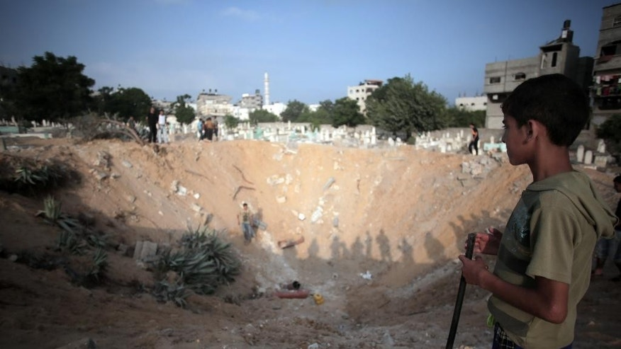 Palestinian check a crater caused by an Israeli strike at a cemetery in the Jabaliya refugee camp, northern Gaza Strip, Monday, July 28, 2014. Monday marked the beginning of the three-day Eid al-Fitr holiday, which caps the Muslim fasting month of Ramadan. Muslims usually start the day with dawn prayers and visiting cemeteries to pay their respects to the dead, with children getting new clothes, shoes and haircuts, and families visiting each other. (AP Photo/Khalil Hamra)