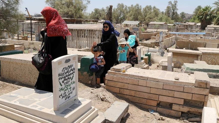 Iraqis visit the grave of a relative on the first day of Eid al-Fitr in Baghdad, Iraq, Monday, July 28, 2014. Monday marked the beginning of the three-day Eid al-Fitr holiday, which caps the Muslim fasting month of Ramadan. Muslims usually start the day by visiting cemeteries, to pay their respects to the dead, and then exchange family visits. (AP Photo/Karim Kadim)