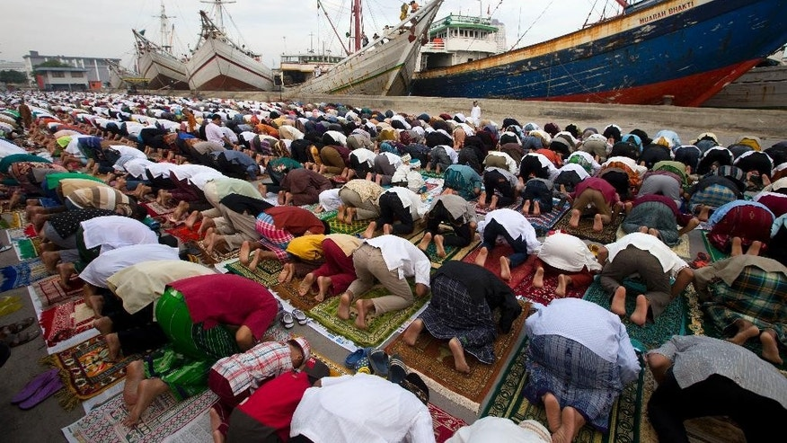 Indonesian Muslims offer Eid al-Fitr prayers at the port in North Jakarta that marks the end of the holy fasting month of Ramadan in Jakarta, Indonesia,  Monday, July 28, 2014.  (AP Photo/Mark Baker)