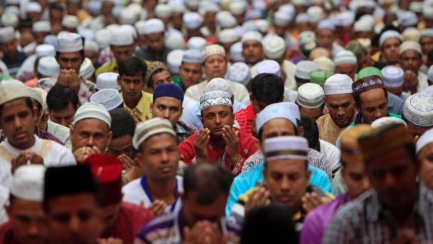 Bangladeshi Muslims living in Malaysia offer a prayer during the first day of Eid al-Fitr, which marks the end of the fasting month of Ramadan in Kuala Lumpur, Malaysia, Monday, July 28, 2014. (AP Photo/Lai Seng Sin)