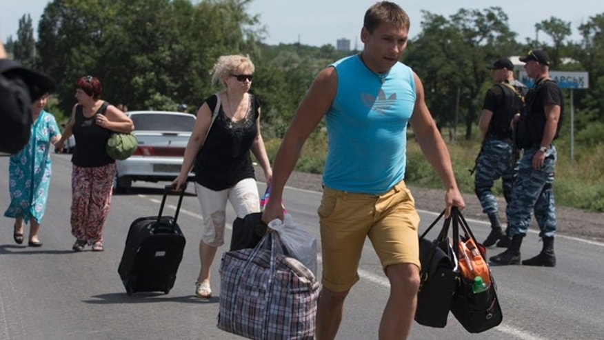 July 28, 2014: Self-proclamed Donetsk People's Republic policemen watch refugees fleeing Shakhtarsk, Donetsk region, eastern Ukraine. An international police team abandoned its attempt to reach the crash site of a Malaysia Airlines plane for a second day running Monday as clashes raged in a town on the road to the area.