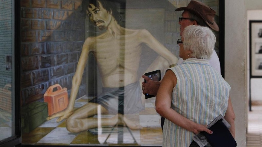 In this July 10, 2014 photo, tourists look at a painting depicting Khmer Rouge torture at the Tuol Sleng Genocide Museum, formerly the most notorious Khmer Rouge prison, in Phnom Penh, Cambodia. The slow course of justice for the leaders of Cambodia's murderous Khmer Rouge regime will inch forward again Wednesday, July 30, 2014 as a U.N.-backed tribunal holds an initial hearing against a pair of defendants in their 80s facing genocide and other charges. Khmer Rouge head of state, Khieu Samphan, and Nuon Chea, right-hand man to the group's late chief, Pol Pot, are among the few surviving top leaders of the brutal communist group, which was responsible for an estimated 1.7 million deaths from starvation, exhaustion, disease and execution when it was in power in 1975-79. (AP Photo/Heng Sinith)