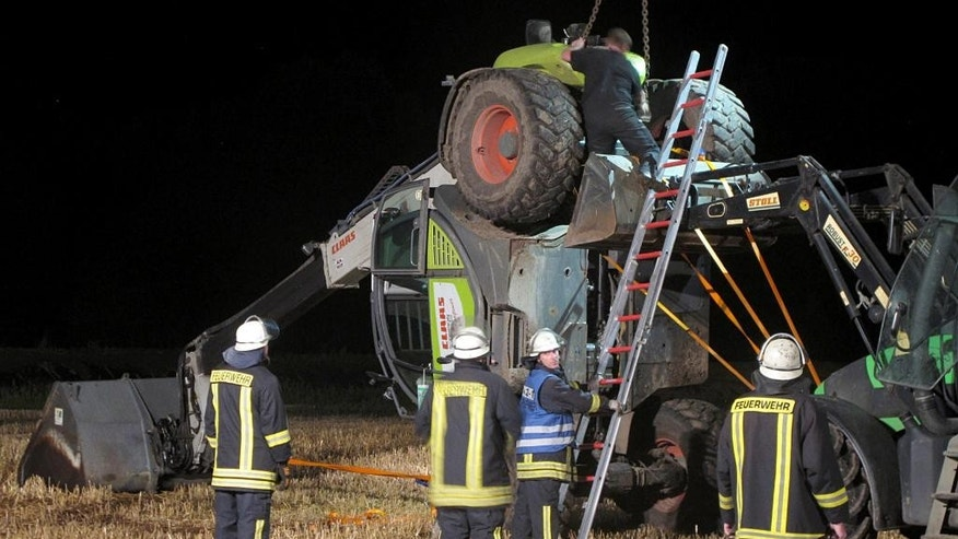 In this picture taken late Tuesday, July 29, 2014, firefighters try to set up a mechanical digger on a field near Isselburg, western Germany. German authorities say a man was killed and several others were injured when the digger tipped over and hit them during a so-called Cod Water Challenge, a dare that has been spreading on Facebook. (AP Photo/dpa, Guido Schulmann)