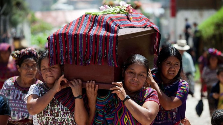 Relatives carry the coffin of one of 31 villagers massacred during the civil war in 1982 in Santa Maria Nebaj, Guatemala, Wednesday, July 30. The remains of 31 Ixil Maya Indians who were killed 32 years ago during the height of the country's civil war have been laid to rest in the country's western highlands. (AP Photo/Moises Castillo)
