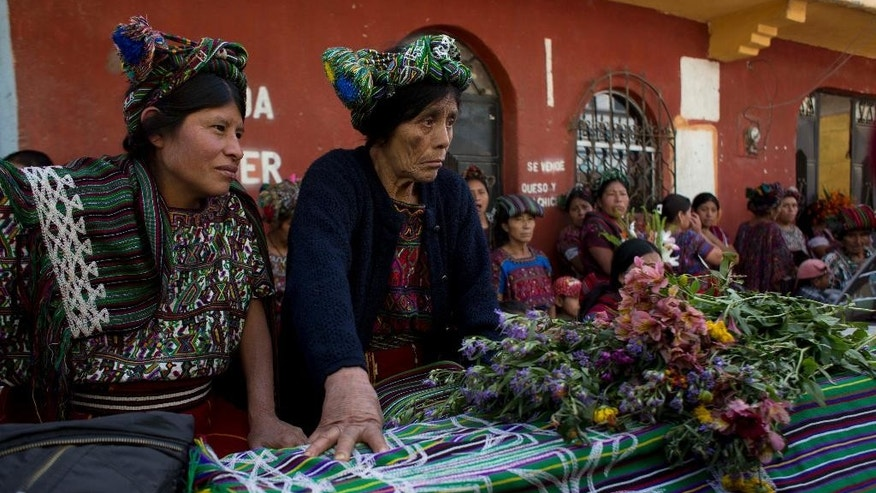 Relatives sit next to the coffin of Miguel Brito, one of 31 villagers massacred in 1982, during their burial in Santa Maria Nebaj, Guatemala, Wednesday, July 30. Brito's remains where one of the 31 Ixil Maya Indians who were killed 32 years ago during the height of the country's civil war have been laid to rest in the country's western highlands. (AP Photo/Moises Castillo)