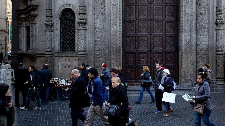 In this Friday, July 25, 2014 photo, pedestrians walk past a branch of the Industrial and Commercial Bank of China, a target for anti-capitalist agitation ever since a 1927 anarchist bombing of what was then a Bank of Boston, in Buenos Aires, Argentina. In 2001, this neo-colonial bank building from Argentina's golden age was ground zero for the country's financial earthquake. Mobs of protesters stared down riot police to demand the return of their savings confiscated by the government in a last-ditch, and ultimately failed, attempt to stay current on its debt. Thirteen years later, a July 30th midnight deadline approaches to avert another default. (AP Photo/Natacha Pisarenko)