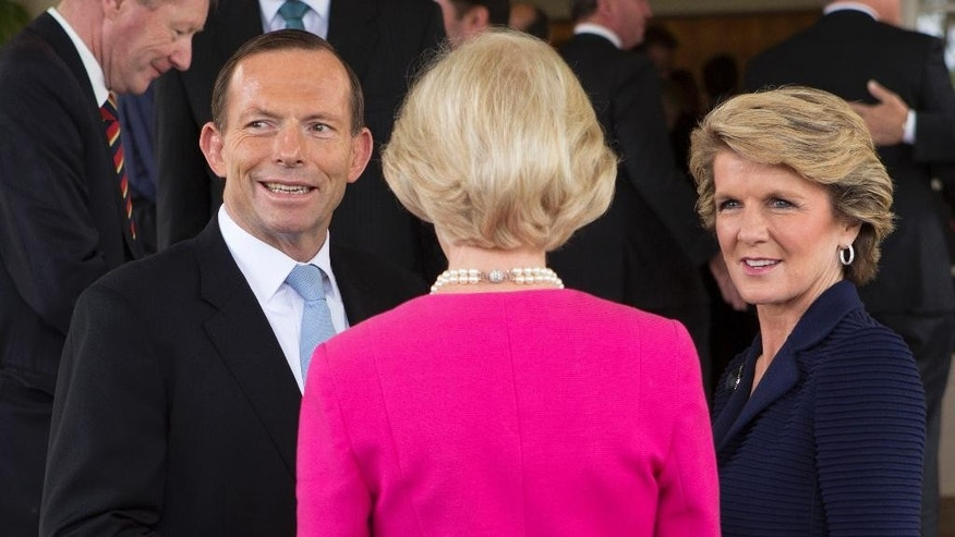 FILE - In this Sept. 18, 2013 file photo, Tony Abbott, left, talks with Foreign Minister Julie Bishop, right, after being sworn in as the 28th prime minister of Australia at Government House in Canberra. Abbott and Bishop on Thursday, July 31, 2014 sent mixed messages on whether Russia was frustrating Dutch and Australian police efforts to retrieve the bodies of victims of the Malaysian airliner disaster in war-torn east Ukraine. Bishop said she feared Russia was behind the daily artillery barrages blocking police, while Abbott said it was too early to judge. Abbott has declined to follow the U.S. and European examples by ratcheting up sanctions against Russia in a bid to pressure President Vladimir Putin into ending his country's support for the separatists. (AP Photo/Penny Bradfield, File)