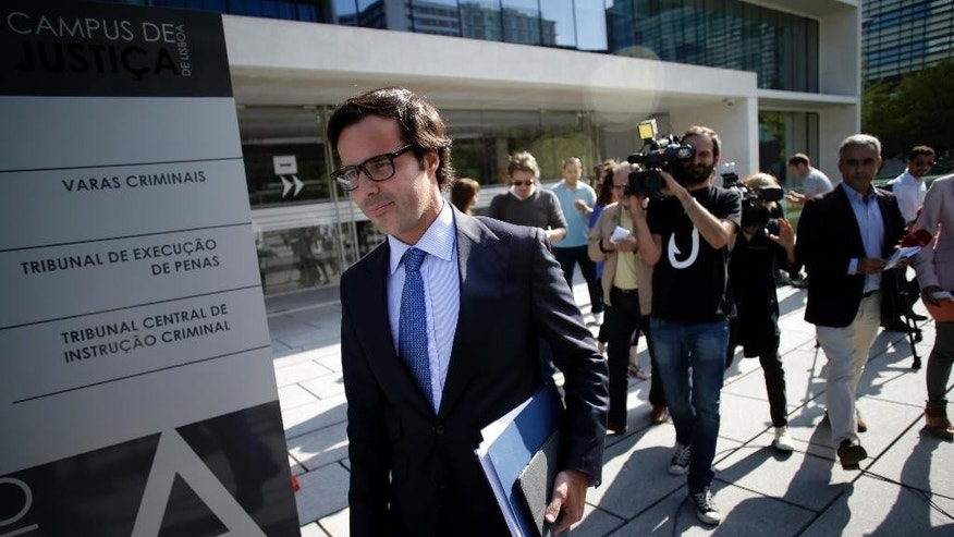 In this July 24, 2014 photo, Francisco Proenca de Carvalho, lawyer for Portuguese bank Banco Espirito Santo's former chief executive Ricardo Salgado, leaves a Lisbon court after Salgado was questioned about money-laundering, fraud and forgery. The Espirito Santo family business survived wars, dictatorship, revolution and family feuds for almost 150 years. Now, one of Europe's last banking dynasties is being stripped of its wealth and influence amid accounting irregularities, huge unreported debts, and a police investigation. (AP Photo/Francisco Seco)