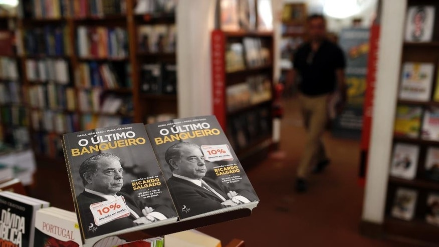 "In this Tuesday, July 29, 2014 photo, a man walks next to books titled ""The Last Banker,"" about former Portuguese bank Banco Espirito Santo's chief executive Ricardo Salgado, in a bookshop in Lisbon, Tuesday, July 29, 2014. The Espirito Santo family business survived wars, dictatorship, revolution and family feuds for almost 150 years. Now, one of Europe's last banking dynasties is being stripped of its wealth and influence amid accounting irregularities, huge unreported debts, and a police investigation. (AP Photo/Francisco Seco)"
