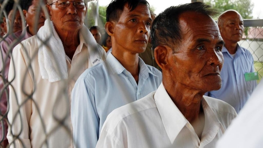 Cambodians line up at a court entrance before a hearing to prepare for the genocide trial of two surviving leaders of Cambodia's Khmer Rouge, at the U.N.-backed war crimes tribunal in Phnom Penh, Cambodia, Wednesday, July 30, 2014.  (AP Photo/Heng Sinith)