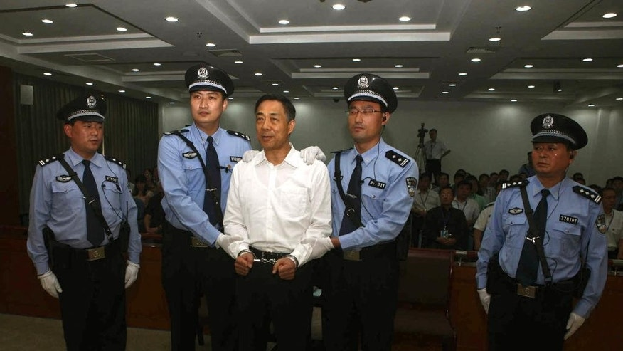FILE - In this Sept. 22, 2013 file photo released by the Jinan Intermediate People's Court, fallen politician Bo Xilai, center, is handcuffed and held by police officers as he stands at the court in Jinan, in eastern China's Shandong province. Bo, the once-rising political star whose wife murdered a British business associate and who was himself accused of rampant bribe-taking was a Zhou Yongkang ally. The investigation into China's former security chief Zhou could pave the way for him to stand trial as the most senior politician ever prosecuted for graft. (AP Photo/Jinan Intermediate People's Court, File)