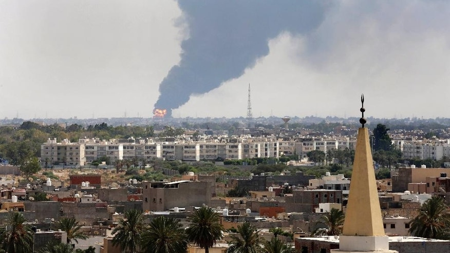"Black smoke billows over the skyline as a fire at the oil depot for the airport rages out of control after being struck in the crossfire of warring militias battling for control of the airfield, in Tripoli, Libya Monday, July 28, 2014. The latest violence to plague the country has so far killed scores of people and wounded hundreds as foreigners flee the chaos. Libya's interim government said in a statement that the fire could trigger a ""humanitarian and environmental disaster"" in Tripoli, appealing for ""international help"" to extinguish the inferno. (AP Photo/Mohammed Ben Khalifa)"