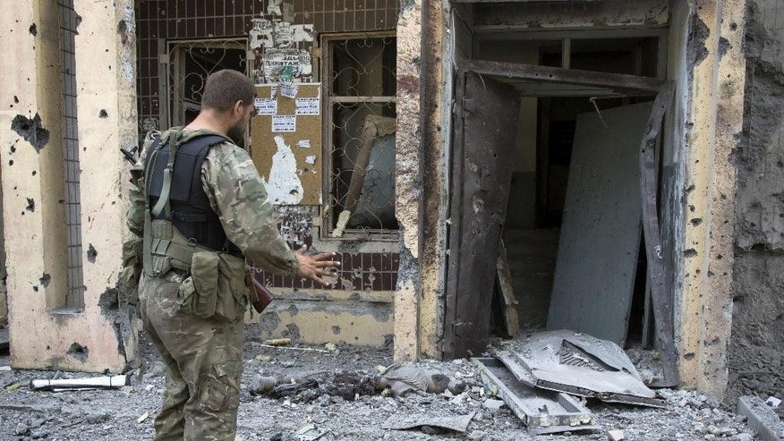 A pro-Russian fighter gestures near a body of a community service worker who was killed during the shelling outside a residential apartment house in Donetsk, eastern Ukraine Tuesday, July 29, 2014.  Local residents said it was a shelling from direction of Ukrainian army's positions. (AP Photo/Dmitry Lovetsky)