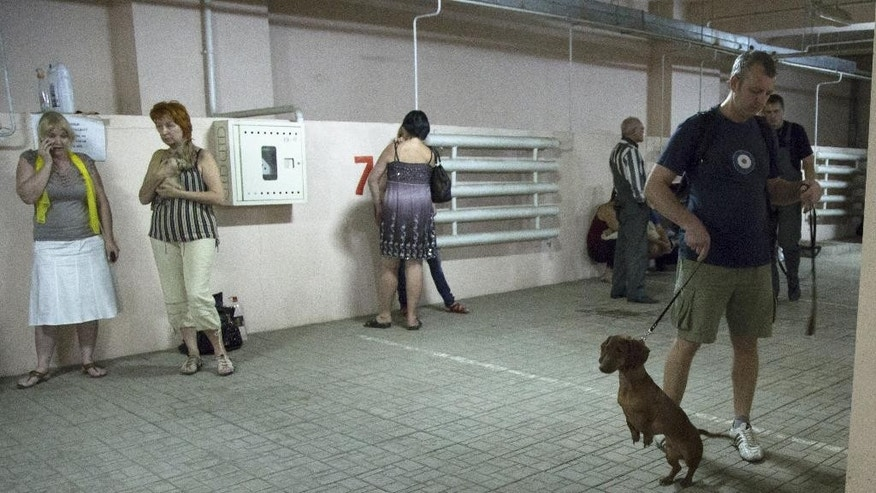 People gather in an underground car park to seek safety from incoming shelling in Donetsk, eastern Ukraine, Tuesday, July 29, 2014. (AP Photo/Dmitry Lovetsky)