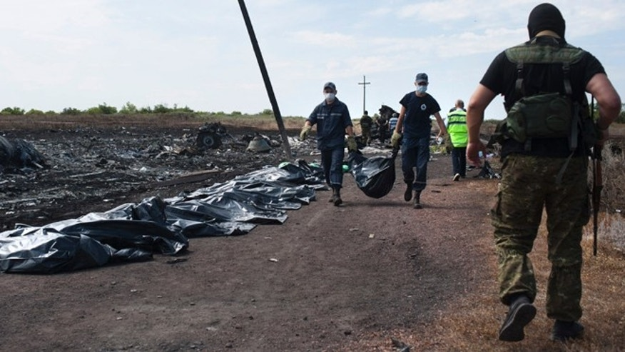 July 20, 2014: Ukrainian emergency workers carry a victim's body in a bag as a pro-Russian fighter, right back to a camera, guards the crash site of Malaysia Airlines Flight 17· near the village of Hrabove, eastern Ukraine.