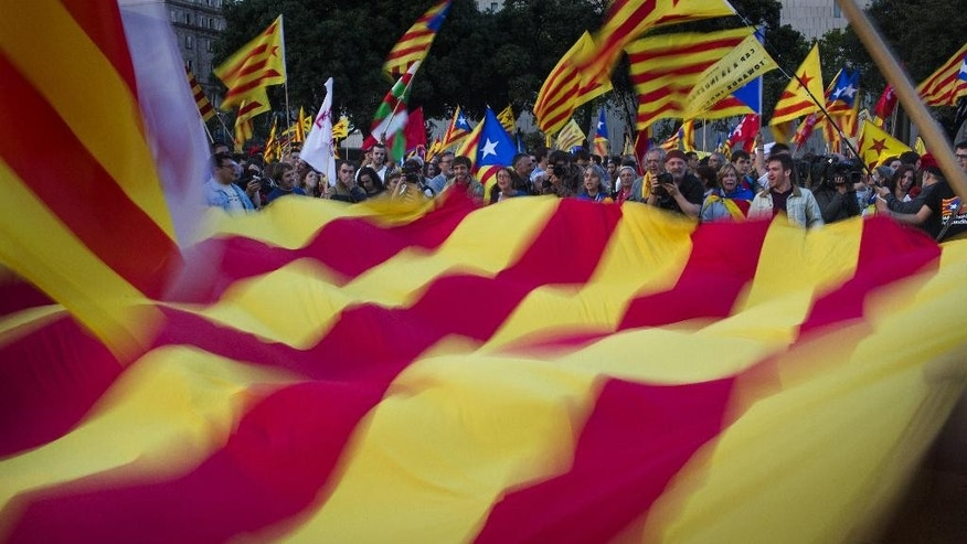 "In this Monday, June 2, 2014 photo, demonstrators wave a pro-independence ""estelada"" flag during a protest calling for the independence and the implementation of the republic in Catalonia after the announcement of the abdication of Spain's King Juan Carlos in Barcelona, Spain. Spanish Prime Minister Mariano Rajoy and the leader of the economically powerful Catalonia region are scheduled to hold a crucial face-to-face meeting on Wednesday, July 30, 2014, in what could be a last chance for the two men to resolve a bitter dispute over the region's plans to hold a secession referendum in November. (AP Photo/Emilio Morenatti)"