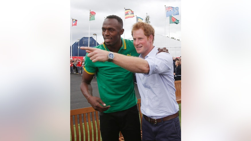 Britain's Prince Harry, right, meets with Usain Bolt during a visit to the Commonwealth Games Village in Glasgow, Scotland, Tuesday, July 29, 2014. (AP Photo/Danny Lawson, PA Wire)