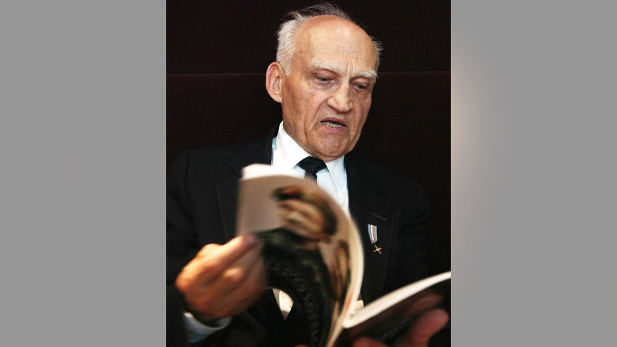 In this photo taken Tuesday, July 8, 2014, Kazimierz Mikos, 84, pages through a booklet devoted to a movie about the 1944 Warsaw Uprising in Warsaw, Poland. As a 14-year-old boy Mikos was a guard and messenger in Warsaw's struggle against the occupying Nazi Germans. He will be among hundreds of fighters attending the ceremonies of the 70th anniversary of the ill-fated struggle that led to the destruction of some 30 percent of the city's substance and the loss of some 200,000 lives. (AP Photo/Czarek Sokolowski)