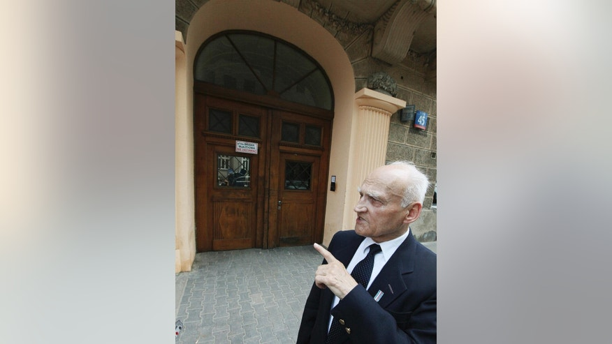 In this photo taken Tuesday, July 8, 2014, Kazimierz Mikos, 84, shows the gateway in Sienna street in Warsaw, Poland, where in the 1944 Warsaw Uprising he secured a live hand grenade, saving the lives of people around him. As a 14-year-old boy Mikos was a guard and messenger in Warsaw's struggle against the occupying Nazi Germans. He will be among hundreds of fighters attending the ceremonies of the 70th anniversary of the ill-fated struggle that led to the destruction of some 30 percent of the city's substance and the loss of some 200,000 lives. (AP Photo/Czarek Sokolowski)