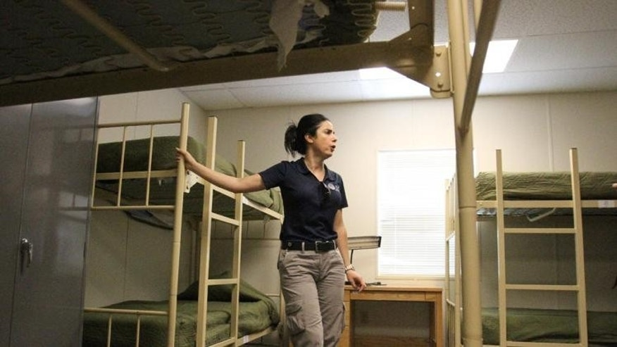 "Barbara Gonzalez, public information officer for Immigration and Customs Enforcement, shows a dormitory where immigrant families are housed at the Artesia Residential Detention Facility inside the Federal Law Enforcement Center in Artesia, N.M. on Friday, July 11, 2014. U.S. Homeland Security Secretary Jeh Johnson visited the facility Friday and warned immigrants that ""we will send you back"" if they try crossing into the country. (AP Photo/Pool, El Paso Times, Rudy Gutierrez)"