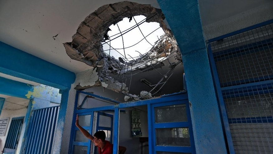 "A displaced Palestinian child waves to a friend from inside a damaged classroom at the Abu Hussein U.N. school, in Jebaliya refugee camp, northern Gaza Strip, Wednesday, July 30, 2014.T he U.N. condemned Wednesday's attack on the school, with Secretary-General Ban Ki Moon calling it ""outrageous"" and ""unjustifiable."" Israel said no U.N. facility had been intentionally targeted, but troops had responded to Hamas mortar fire nearby.  (AP Photo/Lefteris Pitarakis)"