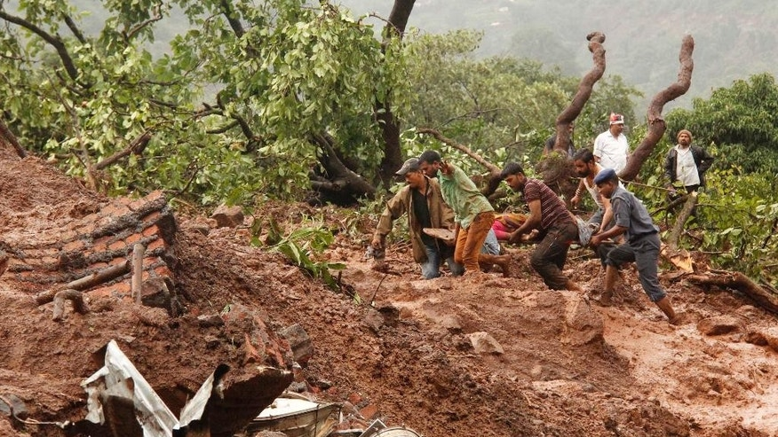 July 30, 2014: Rescue workers carry the body of a victim at the site of a landslide in Malin village, in the western Indian state of Maharashtra. Torrential rains triggered a massive landslide that buried a remote village in western India on Wednesday, killing more than a dozen people as it swept away scores of houses and possibly trapping many more people under debris, officials said.