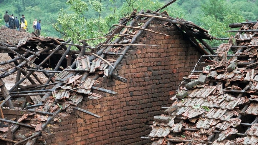 July 30, 2014: Homes stand damaged as rescuers work at the site of a landslide in Malin village, in the western Indian state of Maharashtra.