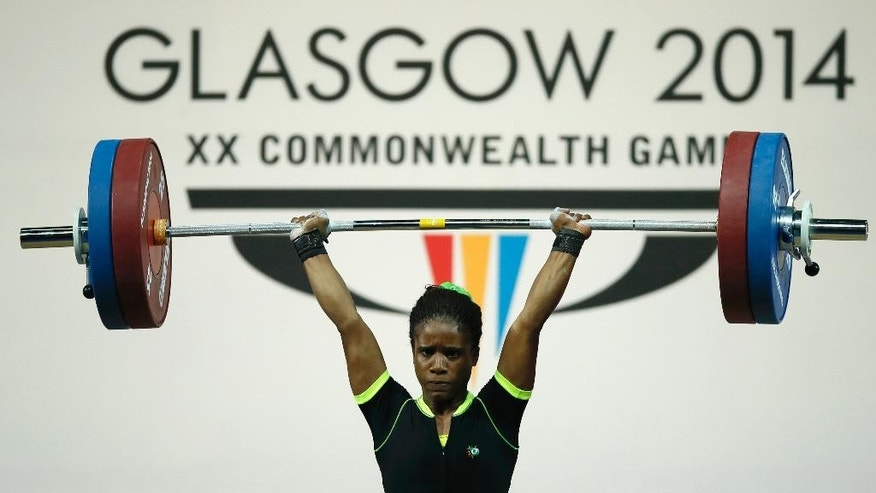 FILE - This is a Friday, July, 25, 2014 file photo  of Chika Amalaha of Nigeria, as she makes good lift during the  women's 53 kg weightlifting competition at the Commonwealth Games Glasgow 2014, in Glasgow, Scotland. Amalaha won the gold medal in the event. The Nigerian weightlifting gold medalist Chika Amalaha has failed a doping test at the Commonwealth Games and has been provisionally suspended from the games. Commonwealth Games Federation chief executive Mike Hooper said Tuesday July 29, 2014 that Amalaha tested positive for diuretics and masking agents after being tested on July 25.  (AP Photo/Alastair Grant, File)