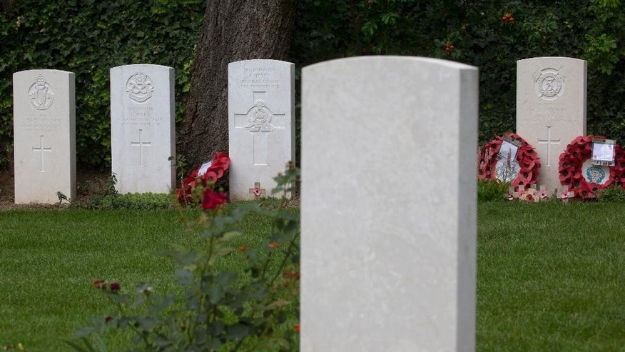 In this photo taken on Saturday, July 26, 2014, the graves of World War I soldiers, Private George Ellison, background right, and Private John Parr, foreground, face each other at the Saint Symphorien Cemetery near Mons, Belgium. Parr and Ellison were the first and the last, respectively, Commonwealth soldiers to die in battle during World War I. Purely by coincidence the graves are separated only by a few feet. (AP Photo/Virginia Mayo)