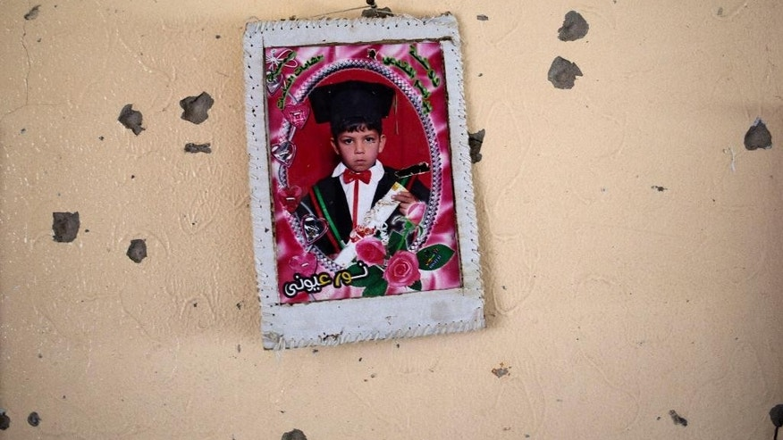 A graduation photo of a Palestinian boy is hung on the wall in a destroyed house in the heavily bombed Gaza City neighborhood of Shijaiyah, close to the Israeli border, Friday, Aug. 1, 2014. A three-day Gaza cease-fire that began Friday quickly unraveled, with Israel and Hamas accusing each other of violating the truce as several Palestinians were killed in a heavy exchange of fire in the southern town of Rafah. (AP Photo/Dusan Vranic)